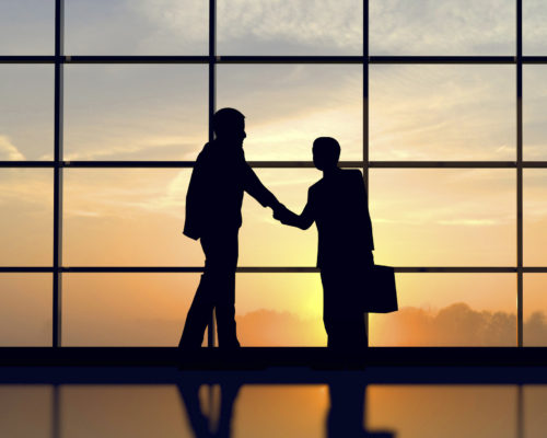 Two business people shake hands against sunset